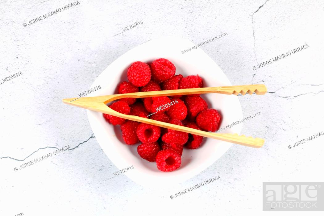 Stock Photo: Raspberries in white bowl with wooden cooking utensil.