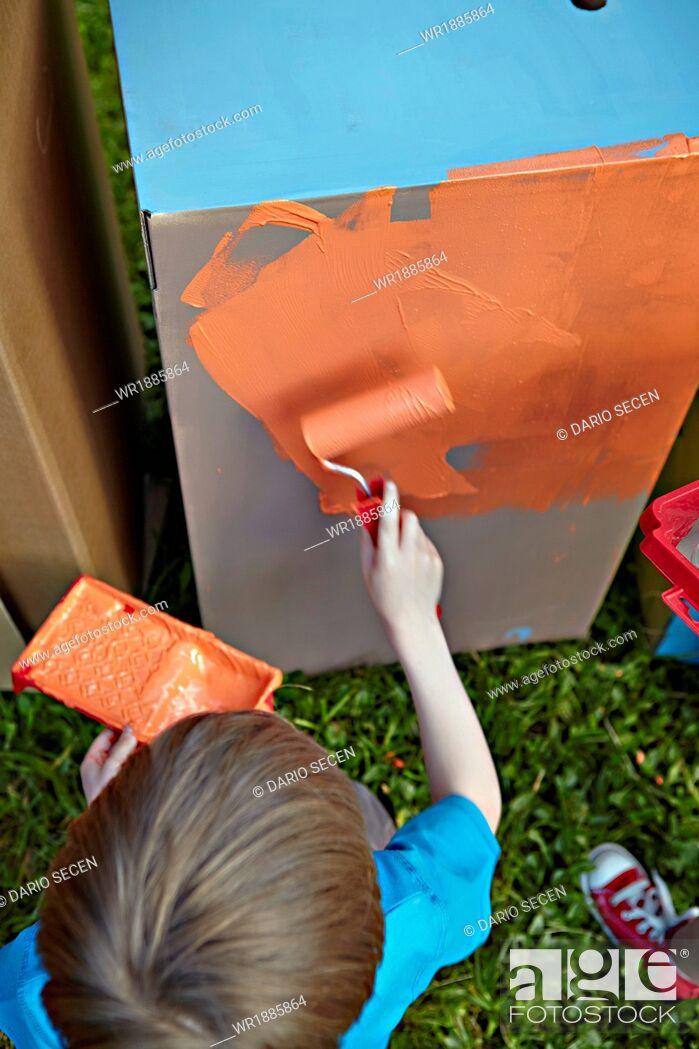 Stock Photo: Boy painting cardboard box, Munich, Bavaria, Germany.