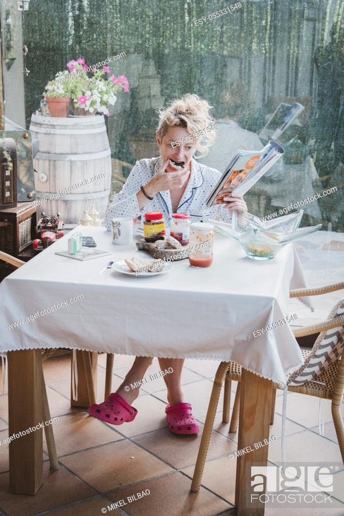 Stock Photo: Blonde young mature woman in pyjamas at home in breakfast time, reading a magazine and eating a toast.
