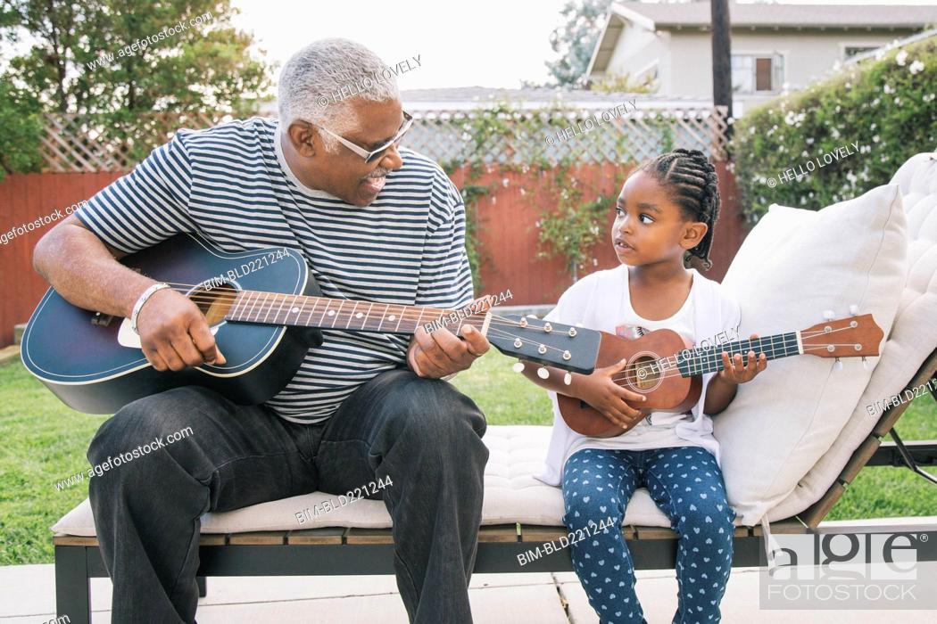 Imagen: African American grandfather teaching granddaughter to play guitar.