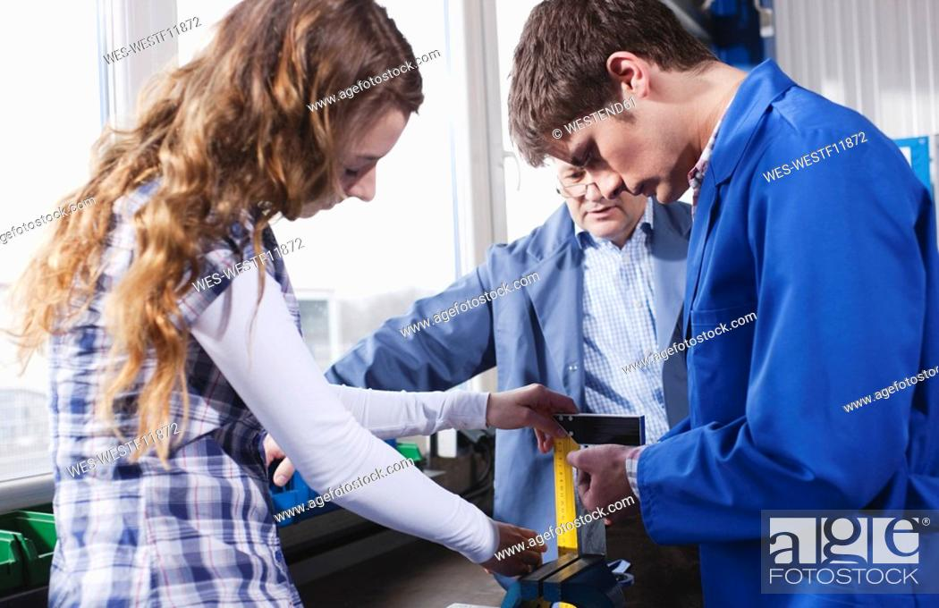 Stock Photo: Germany, Neukirch, Apprentices and instructor.
