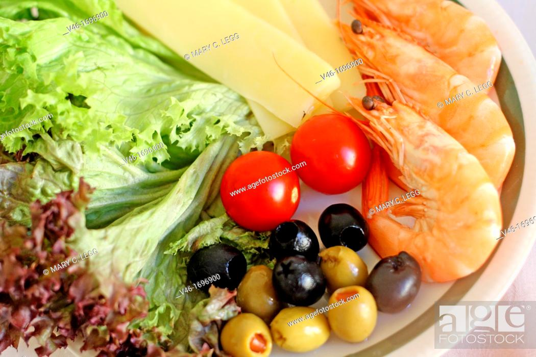 Stock Photo: Salad plate of cheese, olives, tomatoes, shrimp and lettuce on white plate with green trim  White tablecloth  Green and black olives  Full frame.