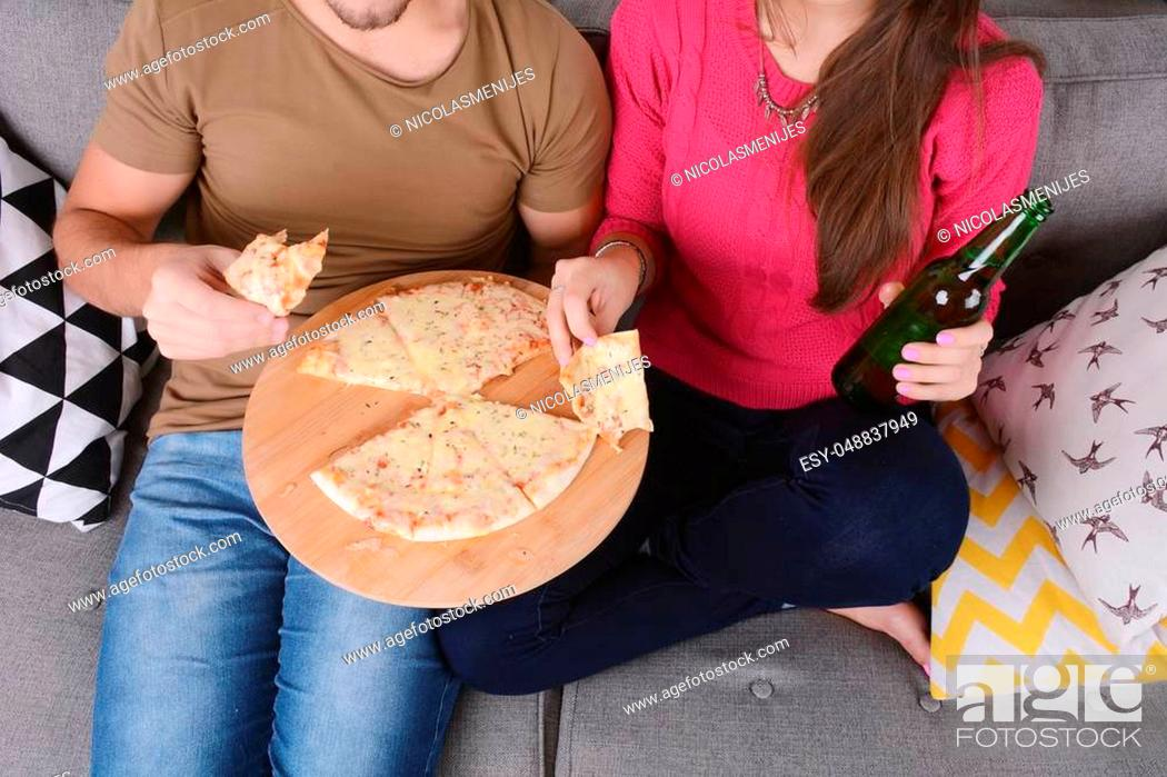Stock Photo: Beautiful young couple drinking beer and eating pizza. Indoors.