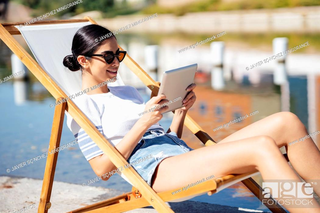 Stock Photo: Smiling young woman sitting in a deckchair using tablet.
