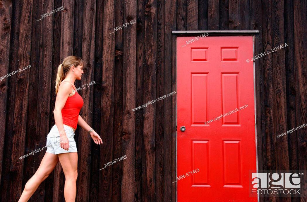 Stock Photo: Woman walks toward red door.