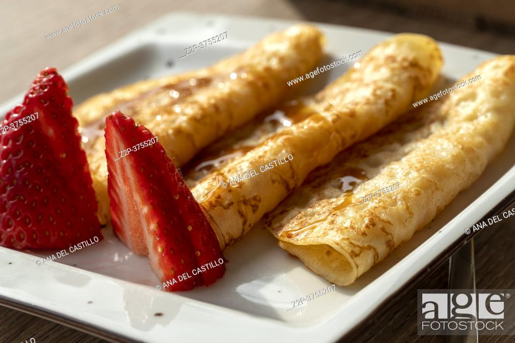 Stock Photo: Three pancakes with slices of strawberries for breakfast in cafe Spain.