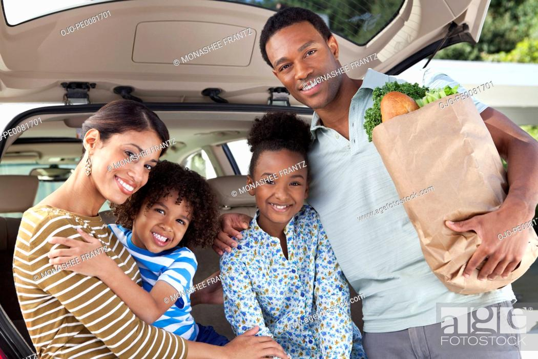 Stock Photo: Family unloading groceries from car.