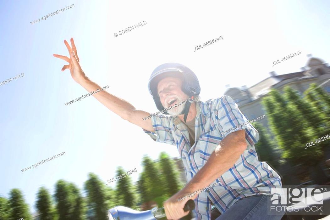 Stock Photo: Man on scooter, waving.