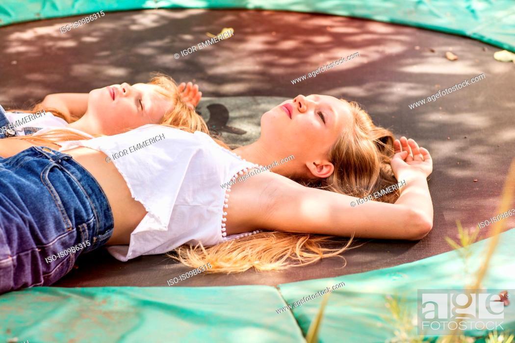 Stock Photo: Girls lying down on trampoline.