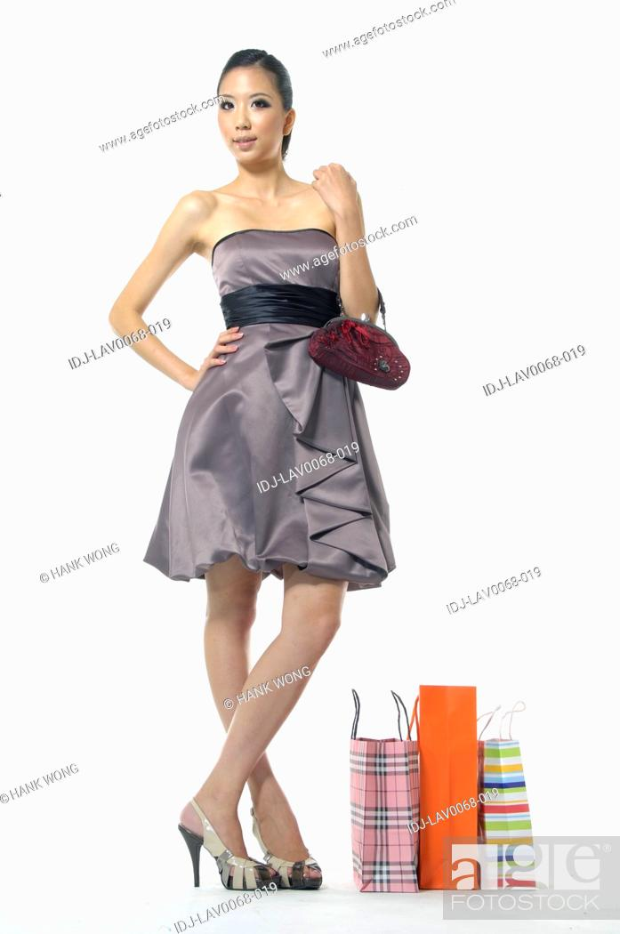 Stock Photo: Woman holding a purse and smirking near shopping bags.