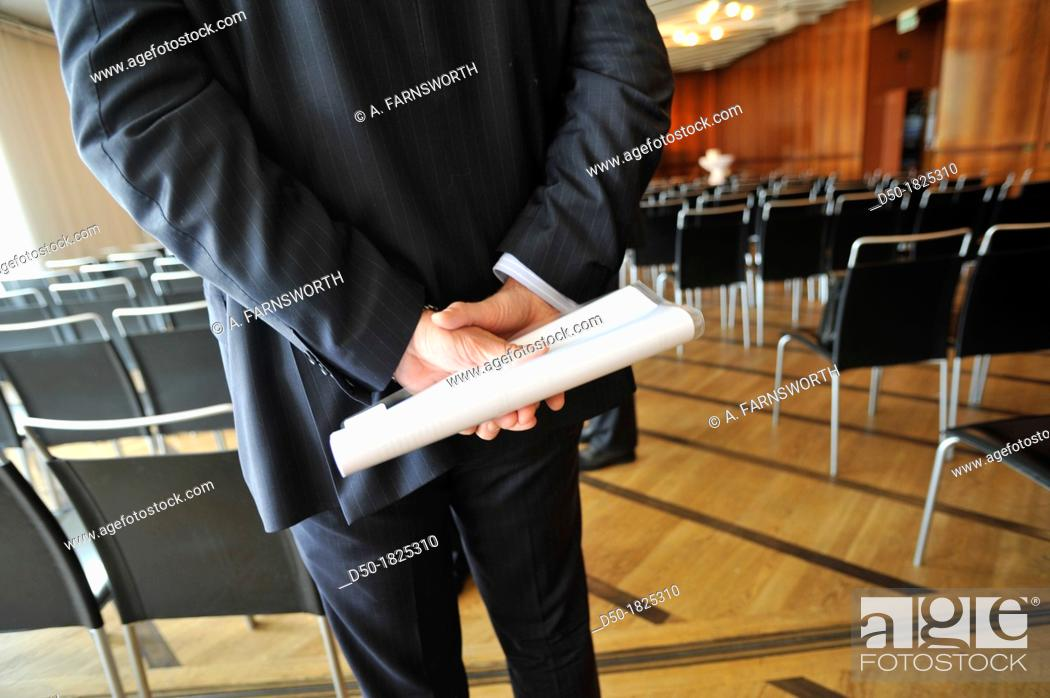 Stock Photo: STOCKHOLM SWEDEN Businessman holding a plastic folder and document behind his back.