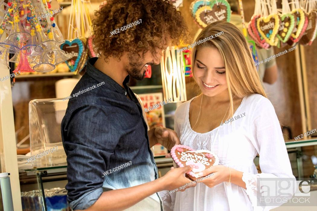 Imagen: Young man gifting his girl friens with a gingerbread heart.