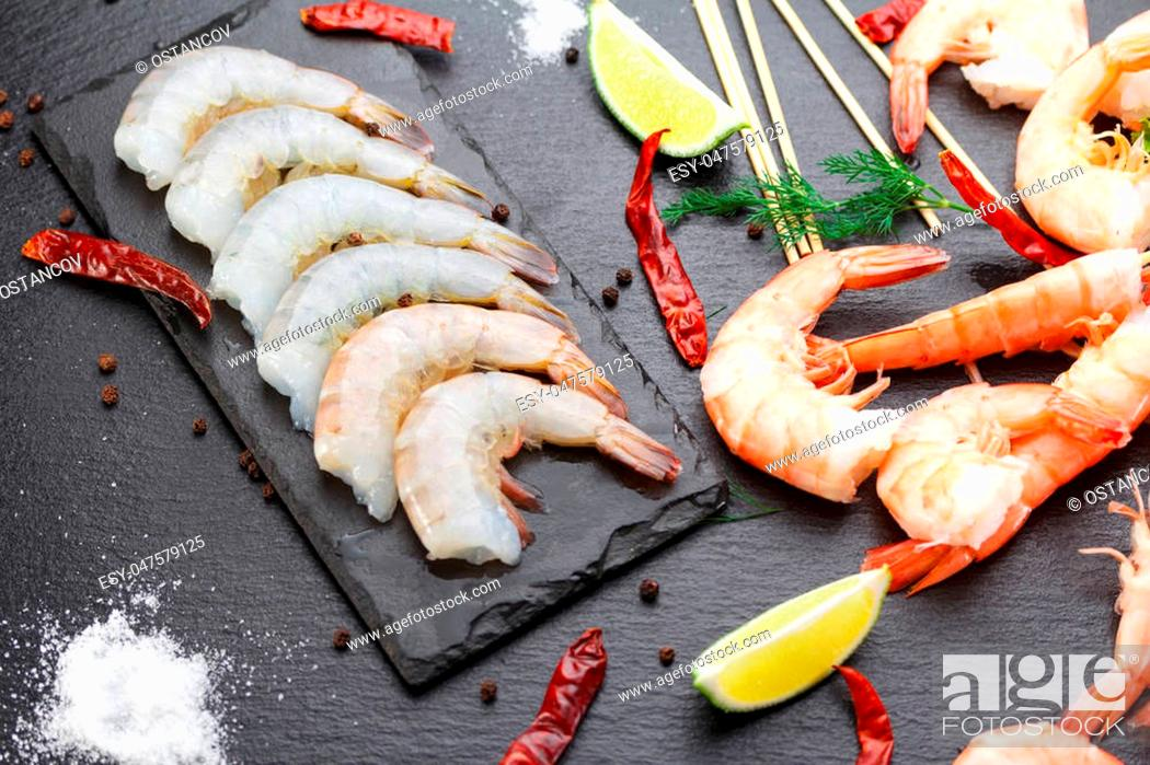 Stock Photo: Raw and boiled shrimps on a stone plate on a black table.