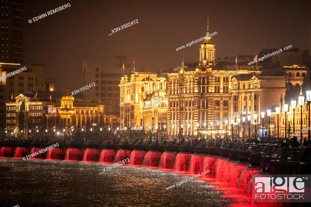 Stock Photo: Color changing lights on the water backed by the bright glow of the Bund , Shanghai, China.