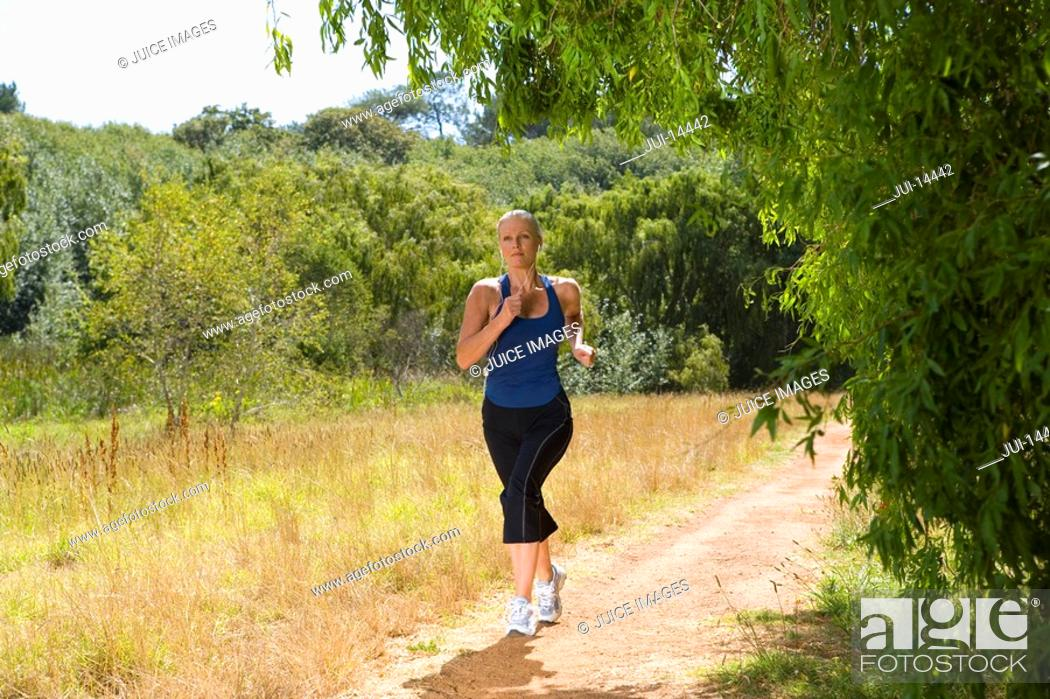 Stock Photo: Woman running on country path, low angle view.