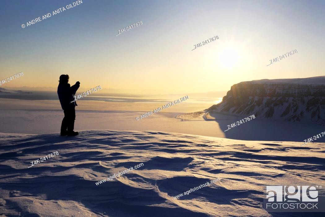 Stock Photo: Expedition member looking over the frozen Tempelfjorden at sunset, Spitsbergen (Svalbard).