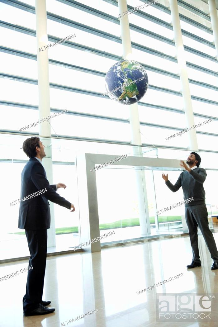 Stock Photo: Businessmen throwing ball in lobby.