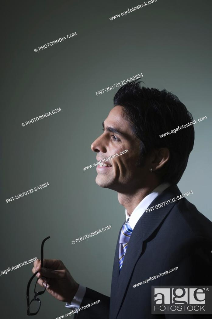 Stock Photo: Side profile of a businessman holding eyeglasses.
