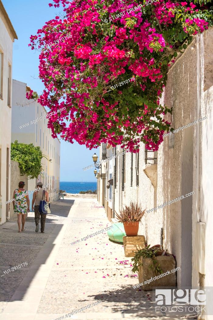 Stock Photo: Couple walk in the shade down a narrow street overhung with Bougainvillea on the island of Tabarca Spain.