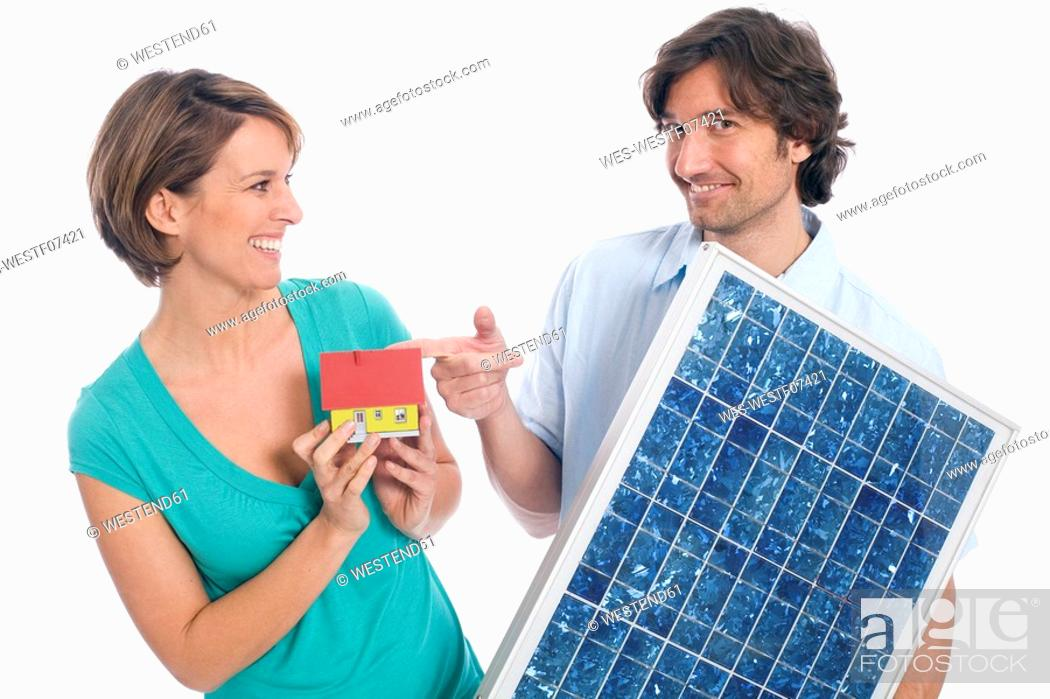 Stock Photo: Couple holding house and solar panel.