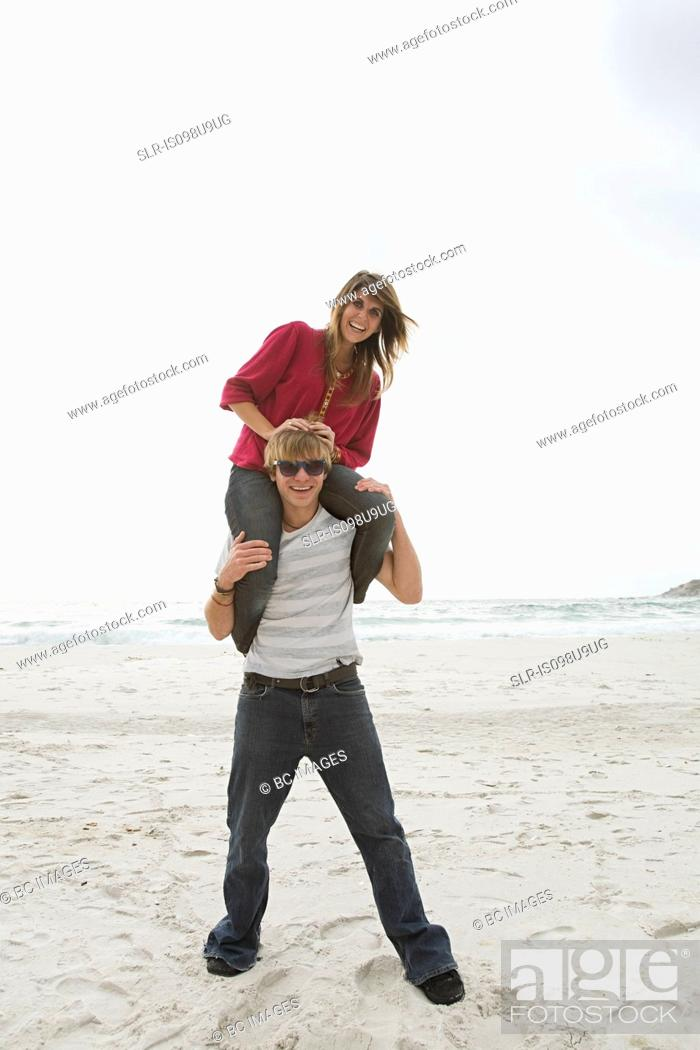 Stock Photo: Young man carrying girl on shoulders on beach.