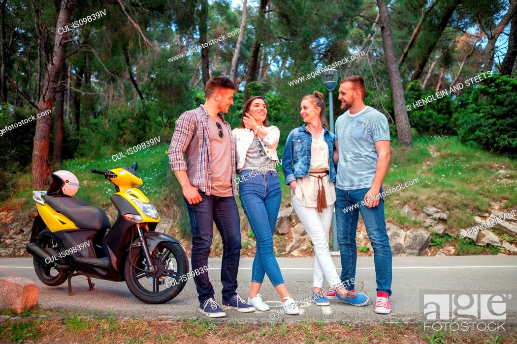Stock Photo: Two couples with moped chatting on rural road, Split, Dalmatia, Croatia.