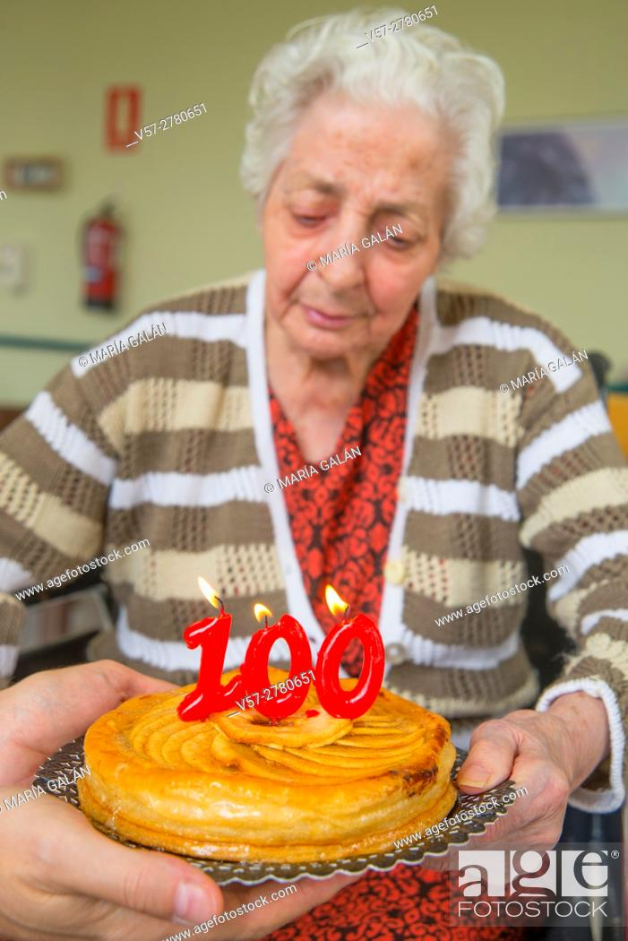 Stock Photo: Old woman in a nursing home, on her one hundred birthday, blowing birthday's candles on a cake held by a man's hands.