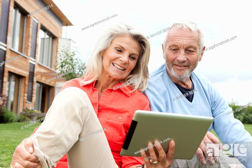 Stock Photo: Germany, Bavaria, Nuremberg, Senior couple using digital tablet in garden.