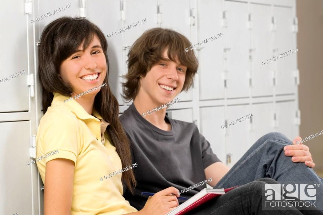 Stock Photo: Portrait of a teenage boy and a teenage girl sitting together and smiling.