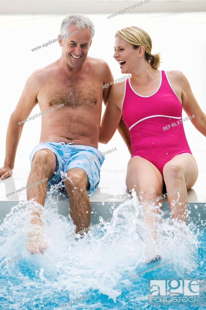 Stock Photo: Senior couple sitting on edge of swimming pool laughing and splashing.