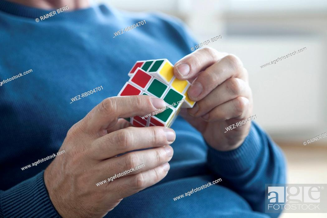 Imagen: Man playing with Rubik's cube.