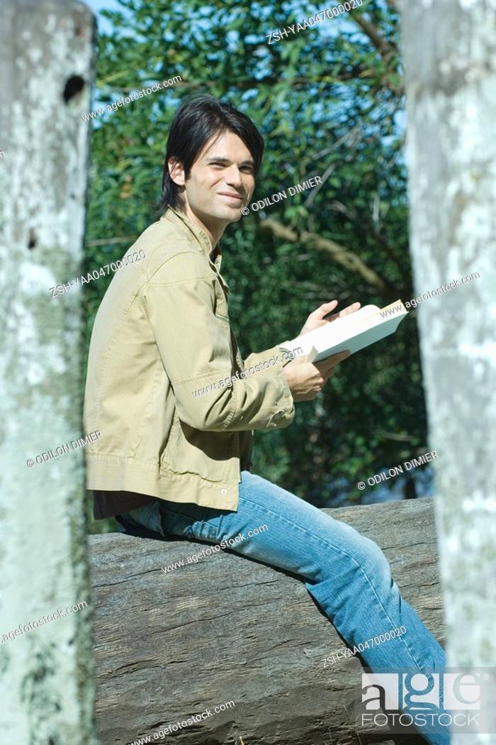 Stock Photo: Man sitting on tree trunk outside, reading book.