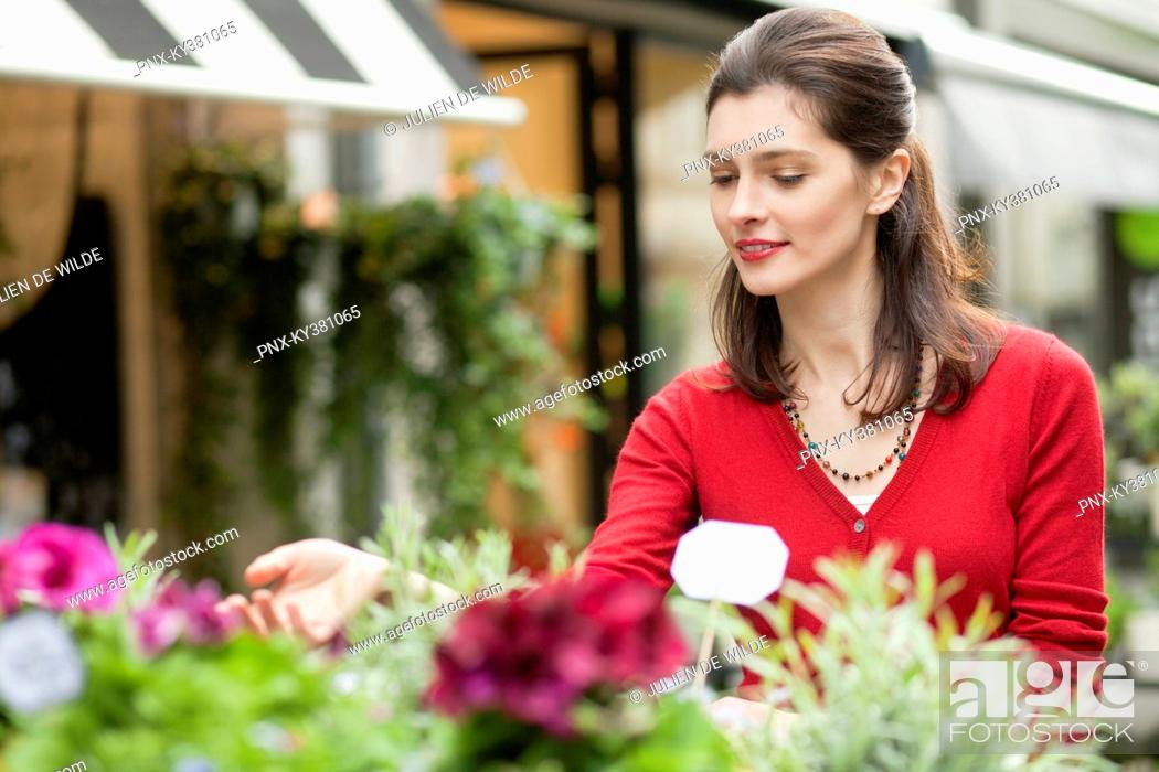 Stock Photo: Woman touching flowers in a flower shop.