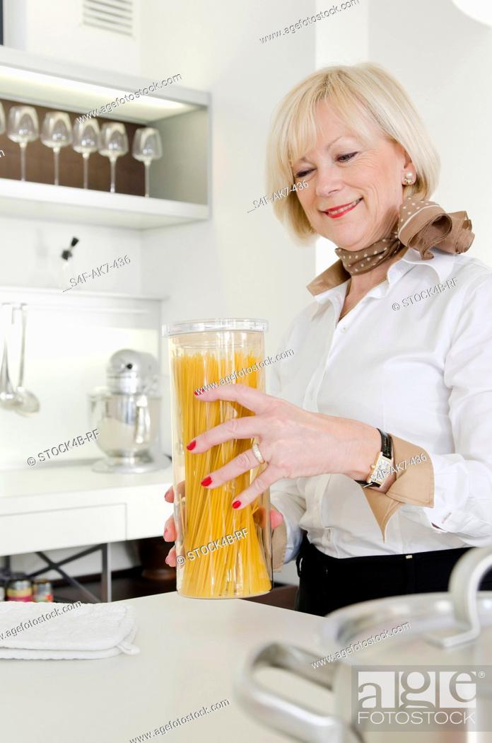 Stock Photo: Senior woman holding Spaghetti glass in kitchen.