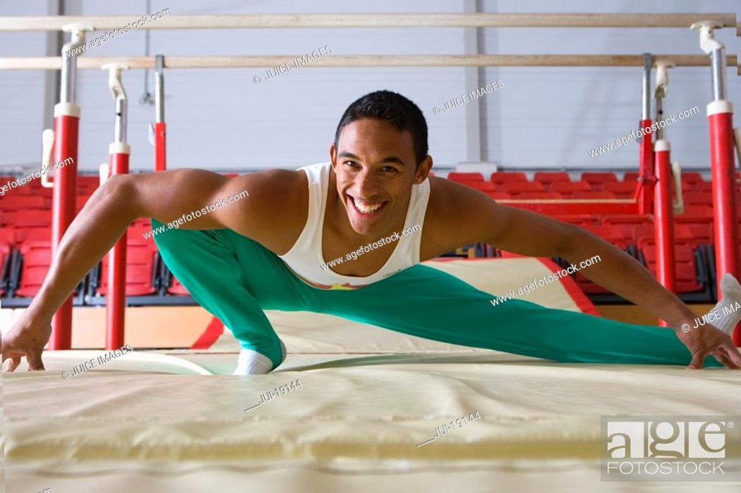 Stock Photo: Male gymnast stretching in gymnasium, smiling, portrait.