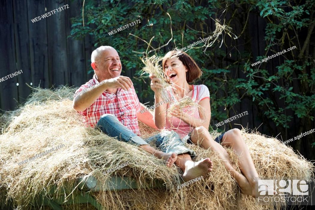 Stock Photo: Germany, Bavaria, Couple sitting on haystack, having fun, portrait.