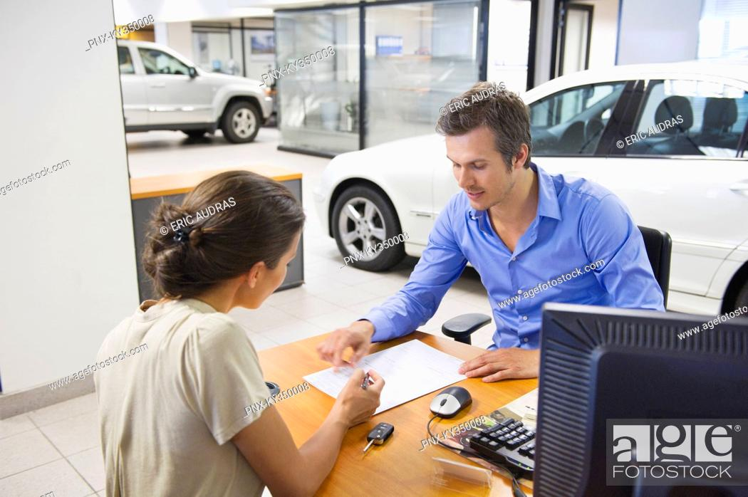 Stock Photo: Mid adult man buying car in a showroom.