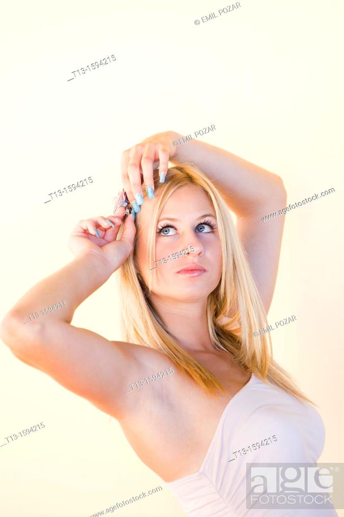 Stock Photo: Attractive young woman is adjusting hair.