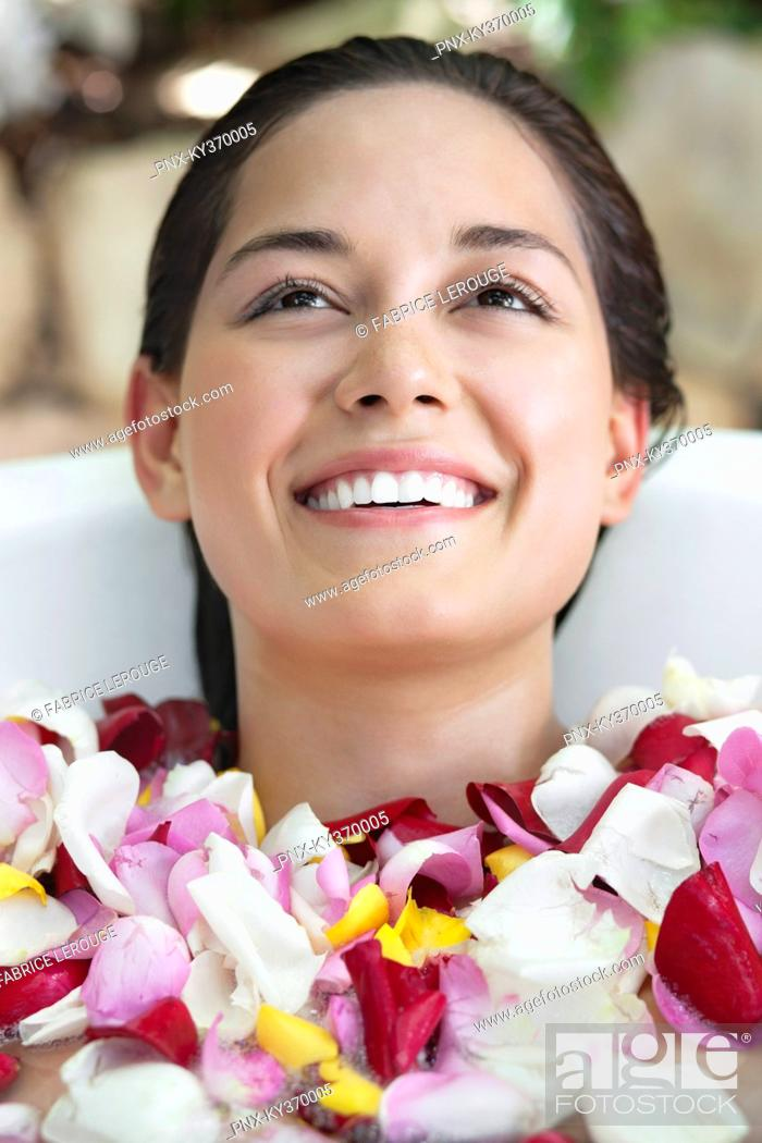 Stock Photo: Beautiful young woman relaxing in bathtub with petals.