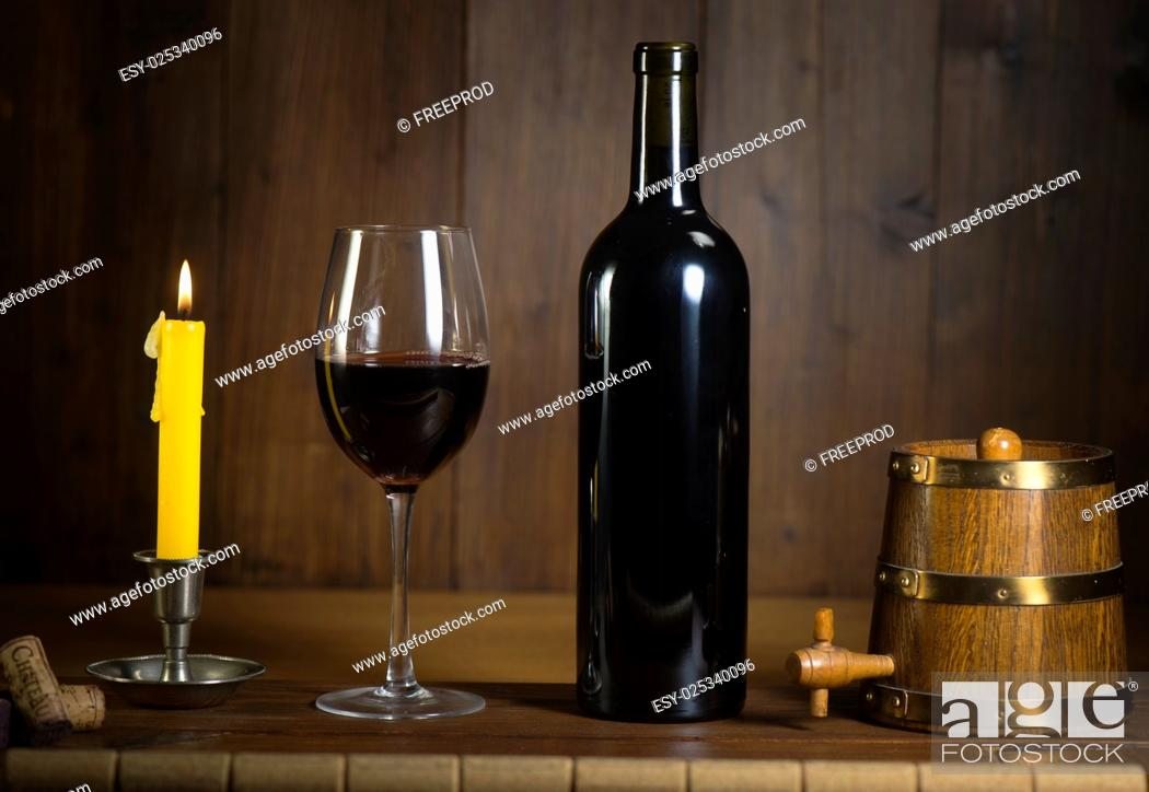 Stock Photo: Pouring red wine into wineglass from green bottle, brown background.