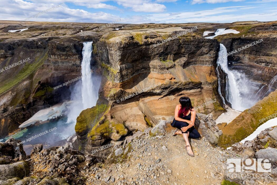 Photo de stock: A young asian female hiker poses for a portrait on the edge of a stunning double waterfall valley landscape known as Haifoss; Iceland.