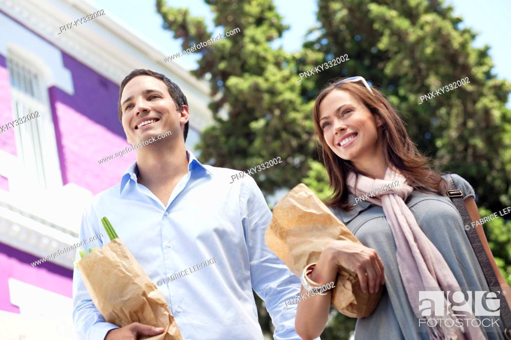 Stock Photo: Smiling couple standing with paper bags full of vegetables.
