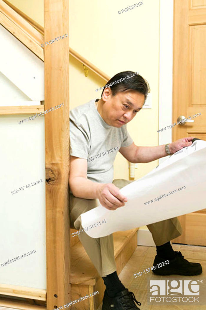 Stock Photo: Side profile of a mid adult man sitting on steps and looking at a blueprint.