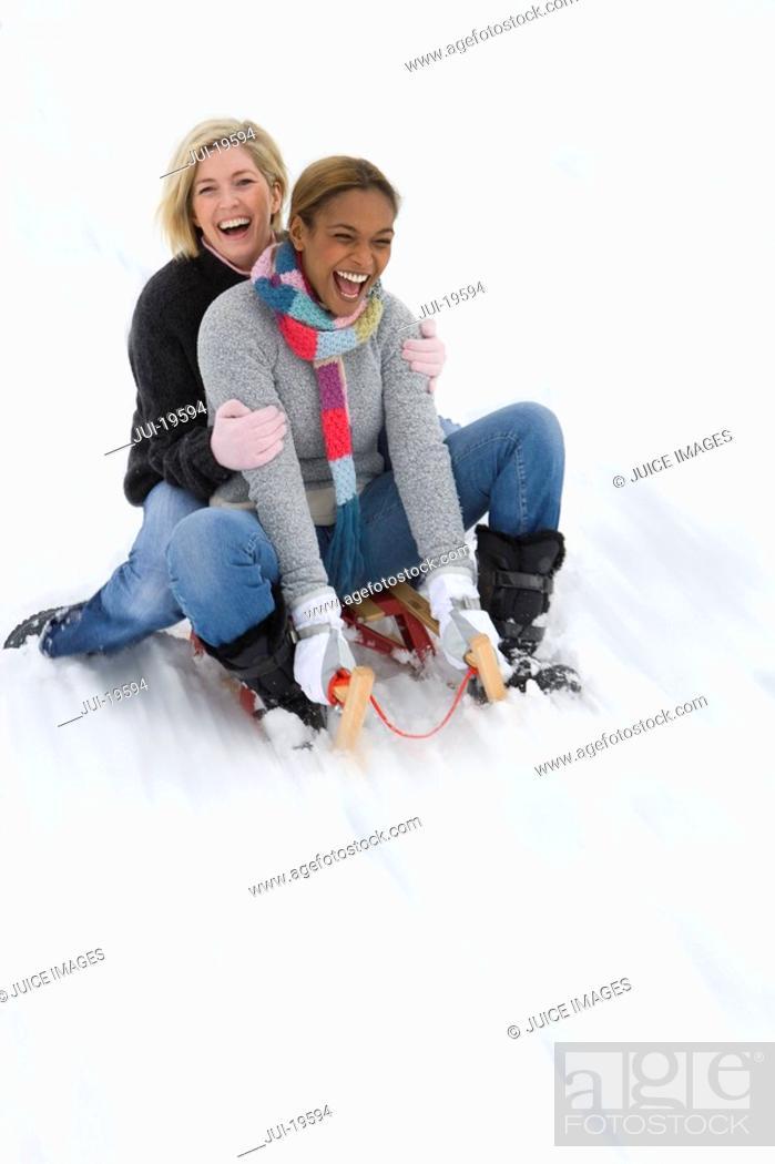 Stock Photo: Women sledding down snow slope.