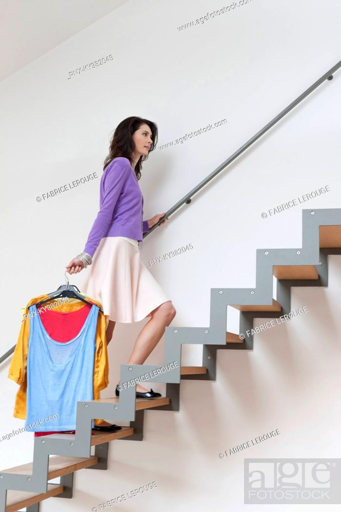 Stock Photo: Woman moving up stairs carrying clothes.