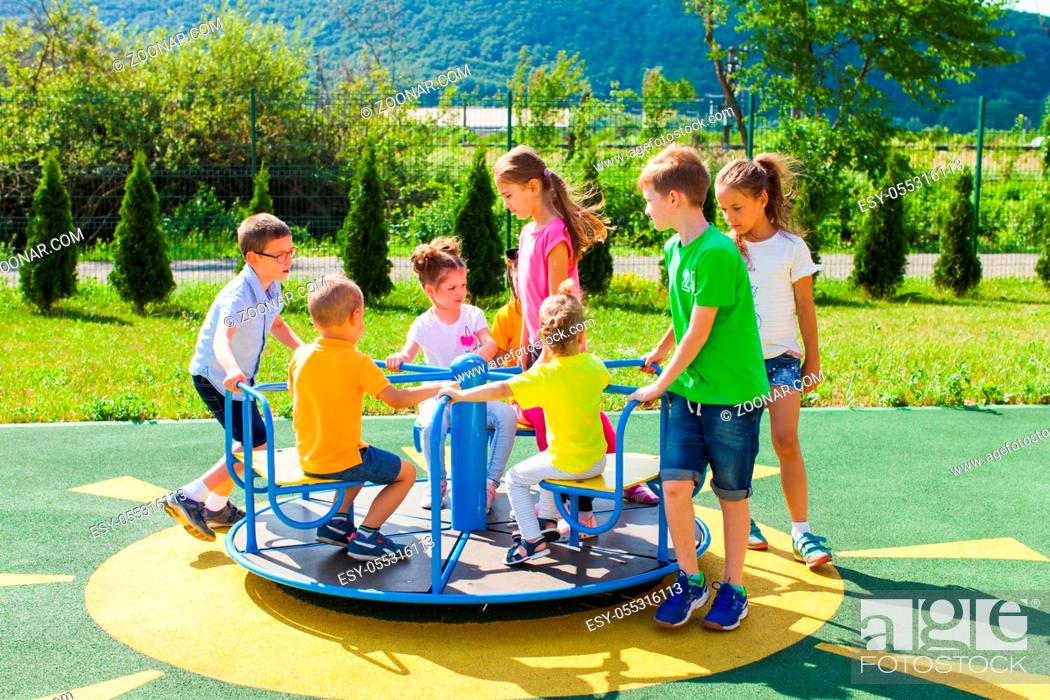 Photo de stock: Cute boys and girls ride on a blue carousel on the playground.