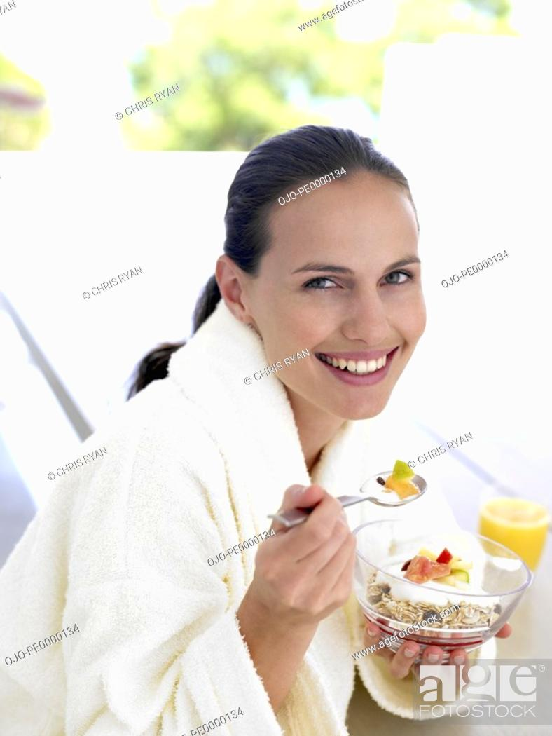 Photo de stock: Woman in robe eating healthy breakfast outdoors.