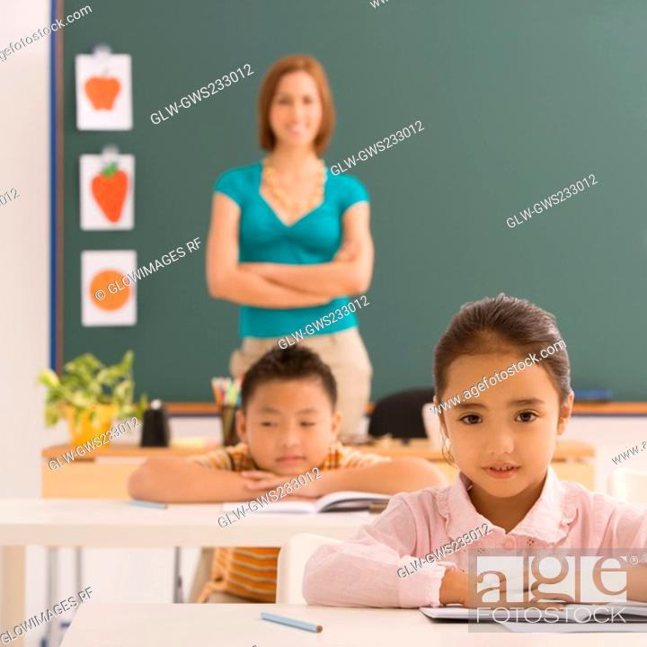 Stock Photo: Schoolgirl sitting in a classroom with a schoolboy and a female teacher in the background.