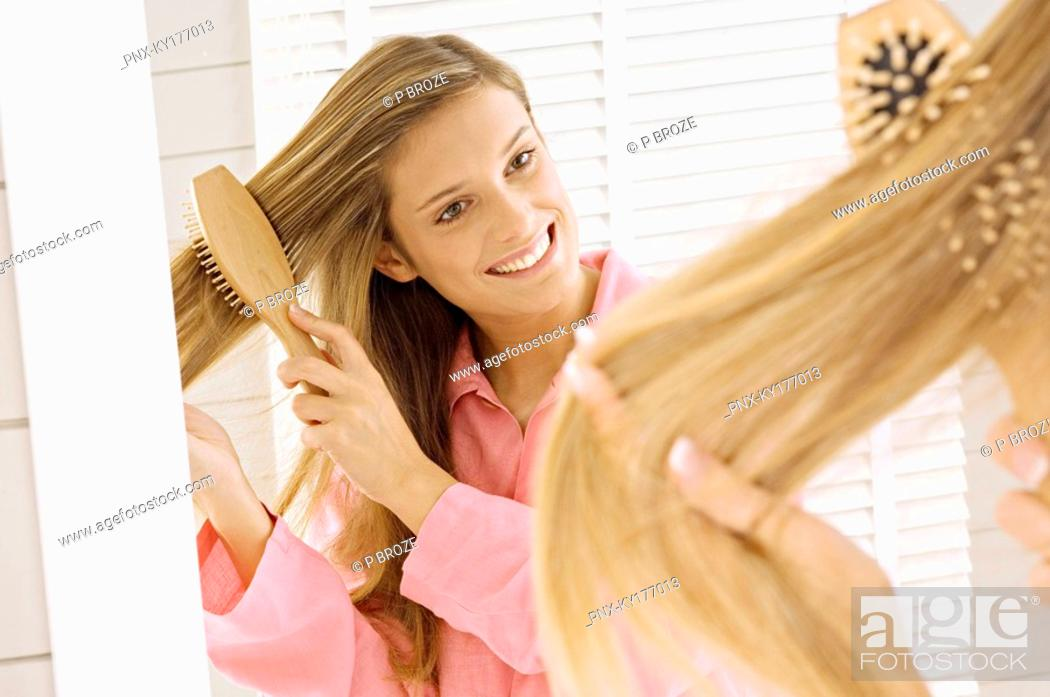 Stock Photo: Reflection of a young woman brushing her hair.