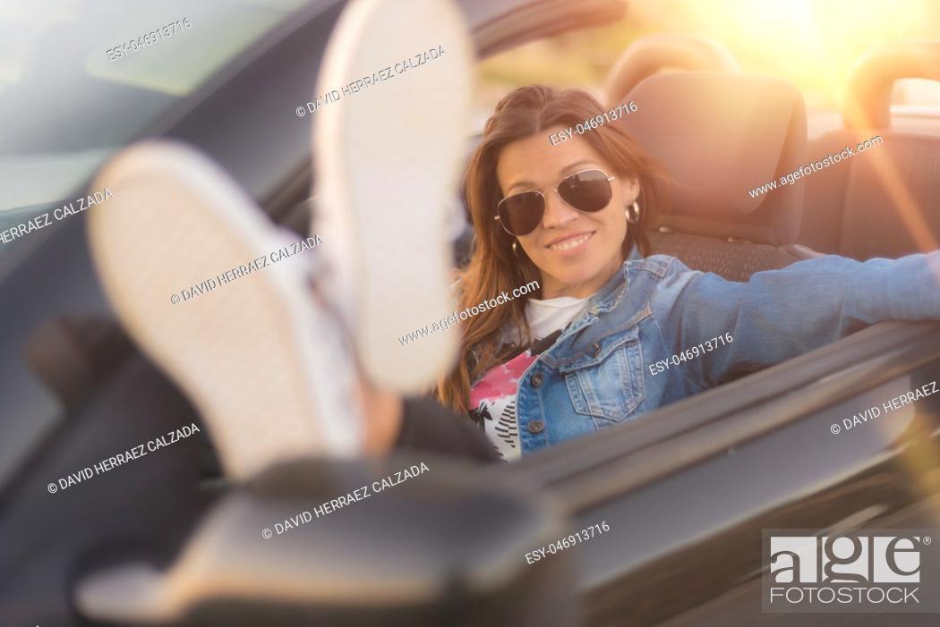 Imagen: Happy young woman enjoying her convertible car.
